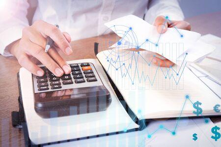 Person, die auf Taschenrechner mit Finanzanalysediagrammen berechnet. Notebook und Taschenrechner liegen auf dem Schreibtisch. Buchhaltung Konzept. Ausgeschnittene Ansicht. Standard-Bild