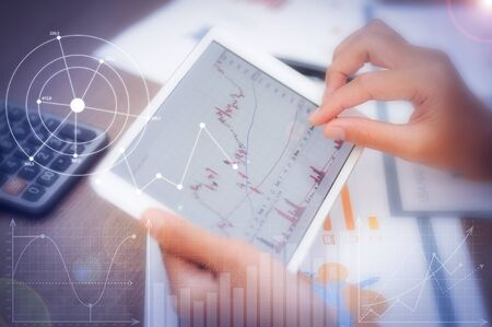 Trader using tablet with financial analysis graphs. Closeup of person working with candlestick chart. Papers and calculator lying on desk. Trading and FOREX concept. Cropped view.