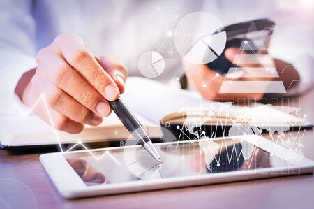 Person pointing pen at tablet with financial analysis graphs. Woman using smartphone and tablet. Technology and planning concept. Cropped view.