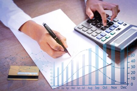 Woman calculating on calculator with financial analysis graphs. Closeup of person writing. Credit card, paper sheet and calculator lying on desk. Payment concept. Cropped view.