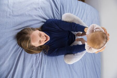 Happy young new mom lying on bed, holding little baby and raising arms. Young woman nursing six month daughter in bedroom at home. Motherhood concept