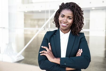Heureux professionnel réussi posant près d'un immeuble de bureaux. Jeune femme d'affaires afro-américaine avec les bras croisés debout à l'extérieur, regardant la caméra, souriant. Concept de chef d'entreprise féminin Banque d'images