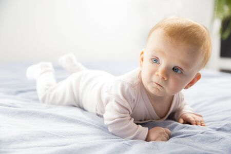 Serious pensive cute baby girl crawling in bedroom. Six month child lying on belly at home. Childhood or baby care concept