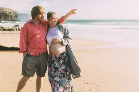 Happy future parents during summer vacation. Smiling husband and pregnant wife standing on beach. Pregnancy concept