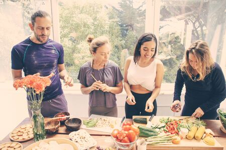 Cheerful friends preparing healthy meal. Happy young man and women in sportswear standing at table with raw organic fruits and vegetables. Healthy eating concept Archivio Fotografico