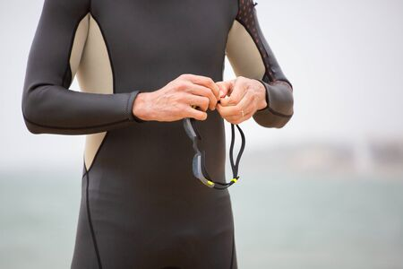 Cropped shot of swimmer holding goggles. Close-up partial view of sportsman in wetsuit holding protective glasses near sea. Triathlon concept
