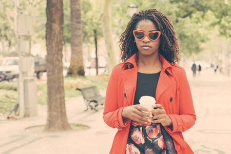 Stylish young woman with coffee to go. Beautiful confident African American woman in red trench coat and sunglasses holding paper cup in park. Fashion concept