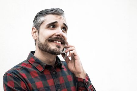Positive man speaking on cell, chatting with girlfriend. Grey haired young man in checkered casual shirt posing isolated over white background. Communication or nice phone talk concept