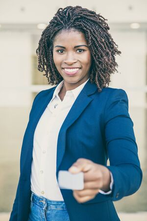 Happy successful consultant giving name card. Business woman wearing formal jacket and jeans, holding blank card, looking at camera, smiling. Name card concept Stock Photo