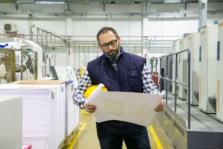 Front view of thoughtful technician inspecting blueprint. Professional printing worker with building plan at factory. Print manufacturing concept