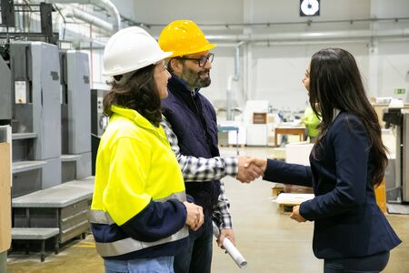 Smiling male factory employee shaking hands with office manager. Cheerful employees communicating at manufacturing plant. Handshake concept