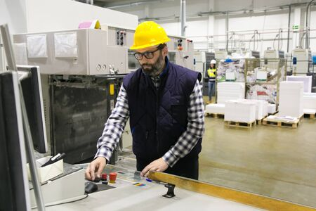 Focused male factory worker operating machine at control panel. Bearded middle aged man in hardhat working at paper mill plant. Automation and production concept