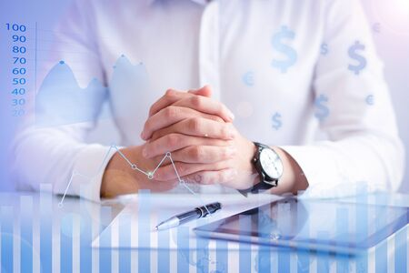Male executive with clasped hands with financial analysis graphs. Close-up of businessman sitting at table. Caucasian HR manager working at table with papers and digital tablet. Employment concept