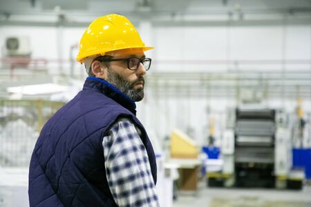 Thoughtful factory worker looking over shoulder. Serious technician controlling working process at plant. Manufacturing concept