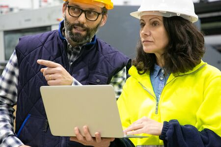 Closeup view of workers talking while standing with laptop. Confident technicians discussing working process. Manufacturing concept Reklamní fotografie