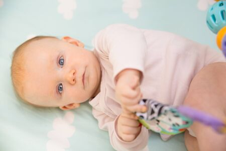Serious beautiful blue eyed baby girl lying in crib, playing with rattle and looking at camera. Six month little child relaxing in bed. Childhood or baby care concept