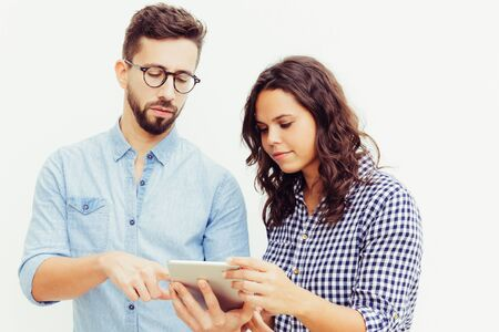 Focused couple with tablet analyzing family budget. Young woman in casual and man in glasses in glasses posing isolated over white background. Personal finance app concept