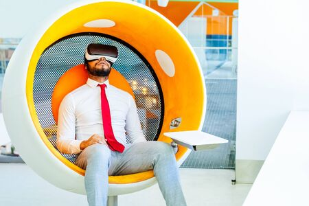 Relaxed businessman using VR headset. Full length view of young African American businessman sitting in spherical chair and using virtual reality headset. Technology concept