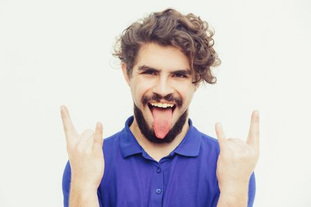 Crazy cheerful rocker sticking out tongue, making devil horns. Handsome bearded young man in blue casual t-shirt posing isolated over white background. Rock-n-roll fan concept