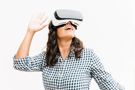 Positive excited female user in VR glasses enjoying experience. Young woman in virtual reality headset standing isolated over white background. VR game test concept