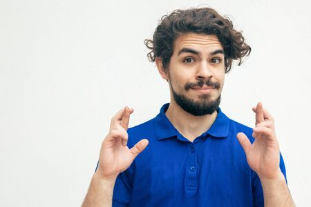 Cheerful positive guy keeping fingers crossed, making wish. Handsome bearded young man in blue casual t-shirt posing isolated over white background. Hope for luck concept