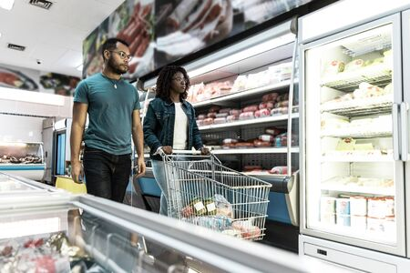 Interracial couple of customers buying food together in grocery store, wheeling cart. Buyers shopping in supermarket. Choosing fresh food concept