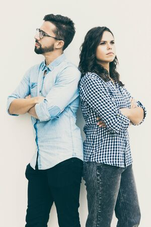 Sad unhappy couple standing back-to-back with arms crossed. Young woman in casual and man in glasses in glasses posing isolated over white background. Breakup concept