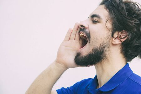 Side of excited guy shouting loud with hand at open mouth. Handsome bearded young man in blue casual t-shirt posing isolated over white background. Advertising concept
