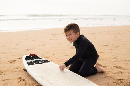 Little boy sitting on sand beach and cleaning surfboard. Smiling kid with short haircut in full body swimsuit. Sea on background. Side view. Vacation, surfing and summer concept Standard-Bild