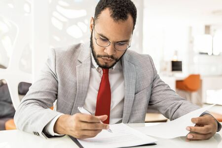 Professional businessman signing contract. Focused young African American businessman in eyeglasses sitting at table and working with documents in office. Paperwork concept