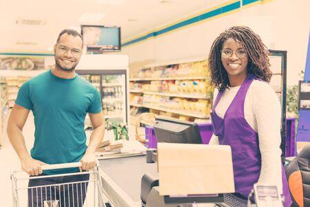 Caissier et acheteur joyeux et joyeux posant au comptoir. Un jeune mélange a couru un homme et une femme debout au comptoir de la caisse enregistreuse dans un supermarché et souriant à la caméra. Concept d'épicerie Banque d'images