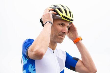 Serious male cyclist wearing helmet. Low angle view of athletic man in sportswear wearing helmet against cloudy sky. Cycling concept