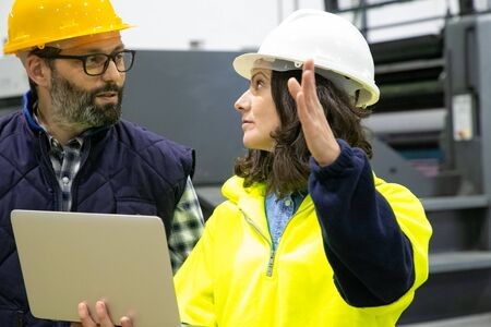 Two factory workers talking while standing with laptop at plant. Confident technicians discussing working process. Manufacturing concept Reklamní fotografie