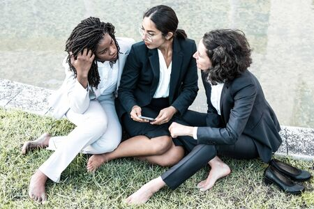High angle view of businesswomen using smartphone outdoors. Group of professional multiethnic businesswomen sitting on lawn and using smartphone together. Technology concept