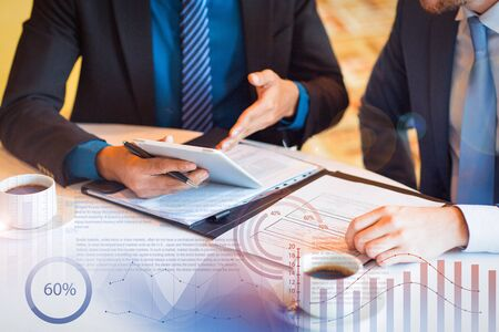 Partners discussing documents and virtual statistic graphics. Cropped view of two business men sitting at table and discussing documents and information on tablet screen