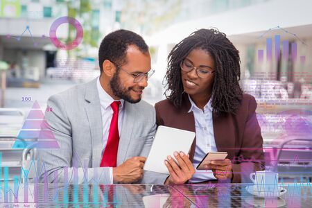 Cheerful coworkers looking at each other gadgets screen with virtual financial graphs around them. Business man and woman sitting in coffee shop. Business and modern technology concept Banque d'images