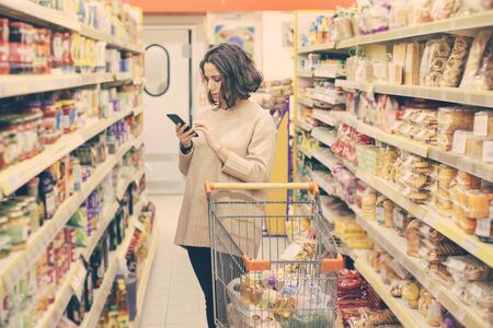 Woman with smartphone choosing goods in store. Focused young woman holding mobile phone and buying products in supermarket. Shopping concept