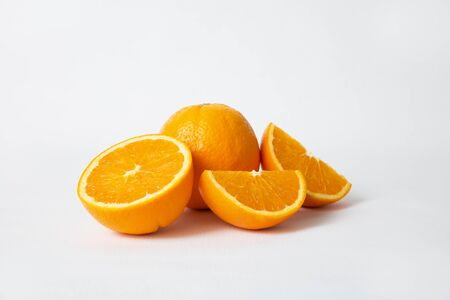 Whole orange fruit and cut slices and half isolated on white background. Closeup shot. Natural vitamin or organic food concept