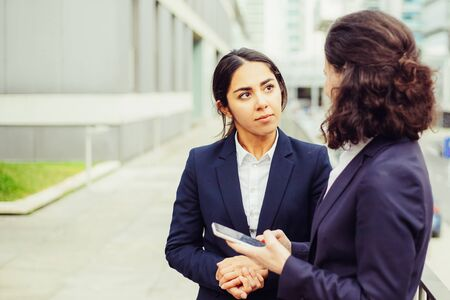 Businesswoman using smartphone and looking at colleagues. Female colleagues in formal wear standing on street with mobile phone and looking at each other. Communication concept