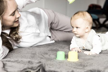 Happy new mom and baby daughter playing learning game on floor. Young woman and six month child enjoying leisure time at home. Motherhood concept