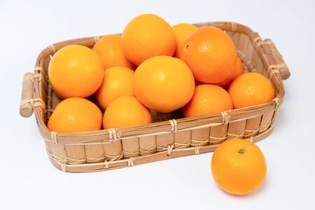 Tasty oranges in wooden basket isolated on white background. One orange laying near basket. Close-up angled view. Citrus fruit and healthy food concept