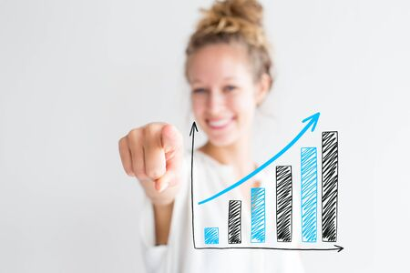 Happy young lovely woman pointing at growing up graphics. Closeup portrait of smiling lady looking at camera and pointing at viewer with focus on hand. Isolated front view on white background.