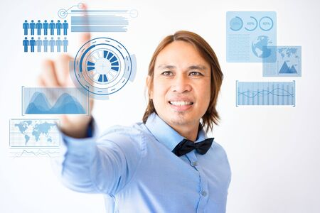 Portrait of smiling young Asian male manager wearing shirt and bowtie touching virtual global infographics. Modern technology in business concept 写真素材