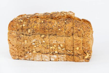 Sliced cereal bread with oatmeal and seeds. Traditional rye loaf cut for sandwiches isolated on white background. Studio shot. Side view. Homemade bakery and cooking at home concept