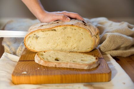 Cook cutting freshly baked bread in slices for breakfast. Rustic burlap sack on table in background. Traditional bread or baking concept Imagens