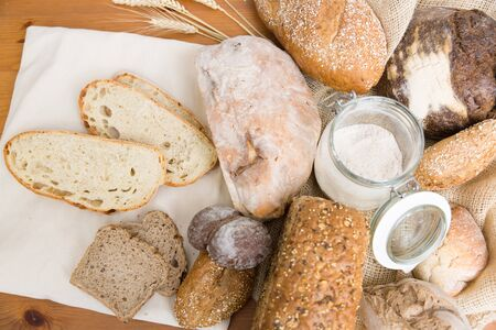 Toasts, loafs and buns of traditional wheat and rye bread, burlap sack, ears and flour. Top view. Wooden table background. Bakery or pastry concept