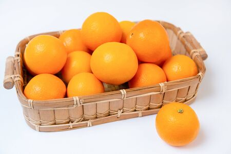 Group of sweet oranges in wooden basket isolated on white background. One fresh orange laying near basket. Close-up angled view. Citrus fruit and healthy food concept