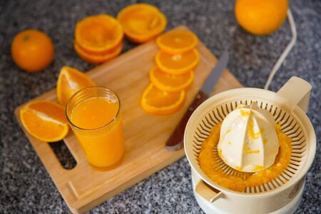 Fresh orange juice in glass making with electric squeezer. Ripe oranges and knife laying on wooden board out-of-focus. Close-up side view. Citrus fruit, kitchen appliance and healthy food concept Stockfoto