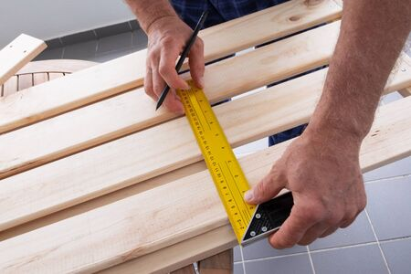 Carpenter measuring distance with construction ruler and drawing marks with pencil on wooden shelf. Senior man working at balcony. House improving and home decoration during quarantine concept Фото со стока