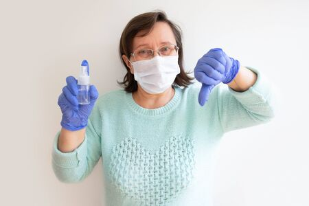 Mature woman in surgical mask holding sanitizer and showing dislike gesture, posing isolated against white background. Front view. Outbreak or disinfection concept